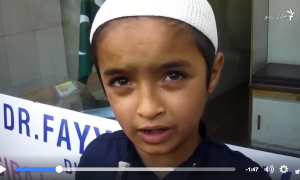 screenshot of video with a closeup of a young boy wearing a white cap
