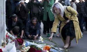 A woman lays flowers at an impromptu memorial