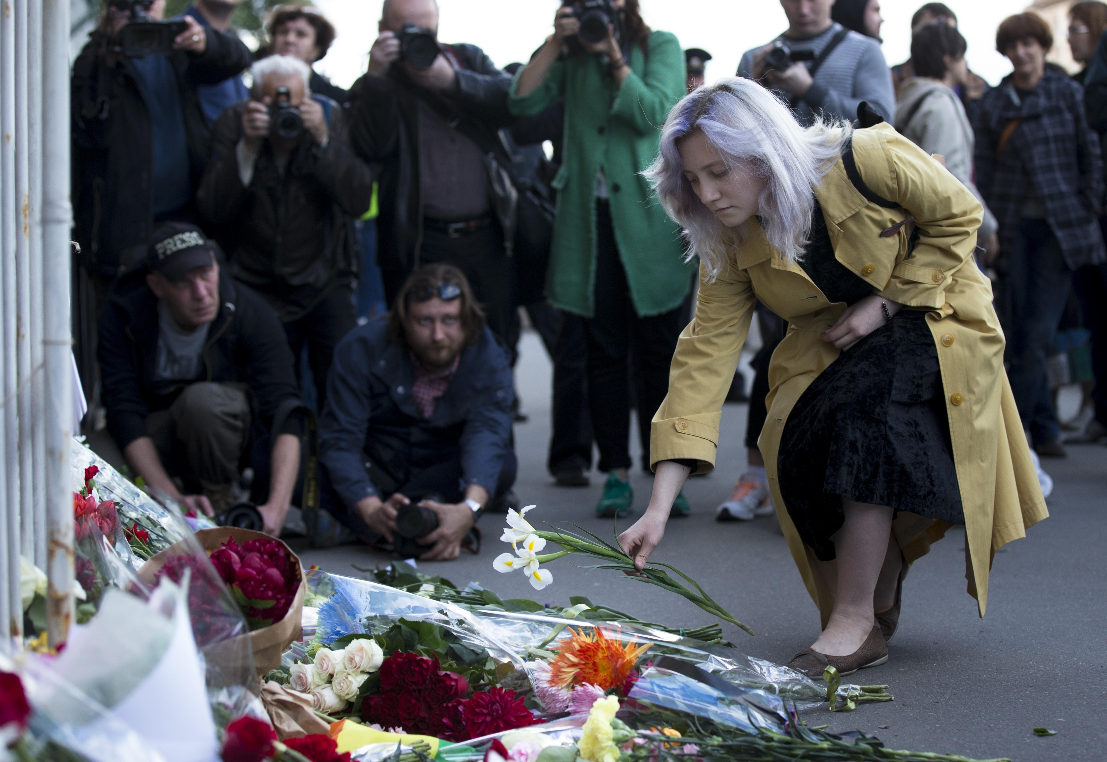 A woman lays flowers at an impromptu memorial