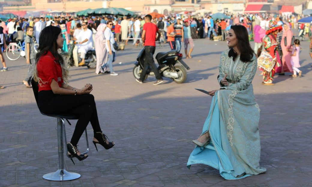 two women sit on stools in the street - one is interviewing the other
