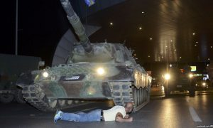 Man lies on the street in front of a tank at night