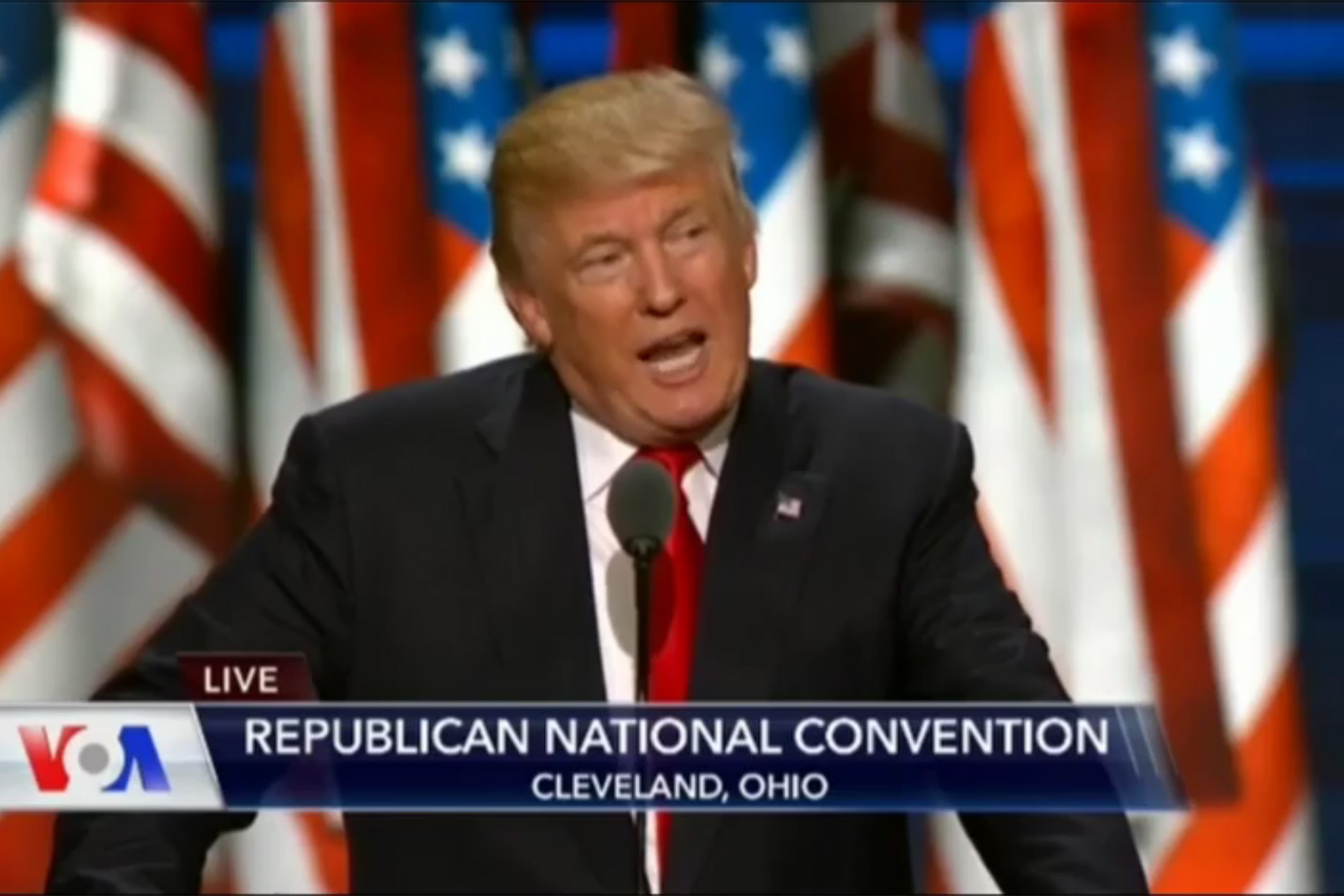 Donald Trump speaking in front of several American flags in the background