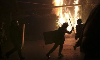 silohuette of a policeman raising his baton, a fire burns behind him