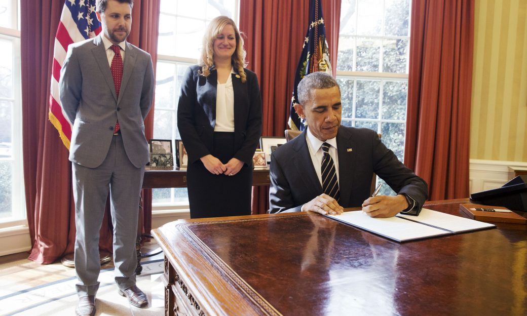 U.S. President Barack Obama signs a paper at his desk in the Oval Office while 2 aides look on from behind his chair