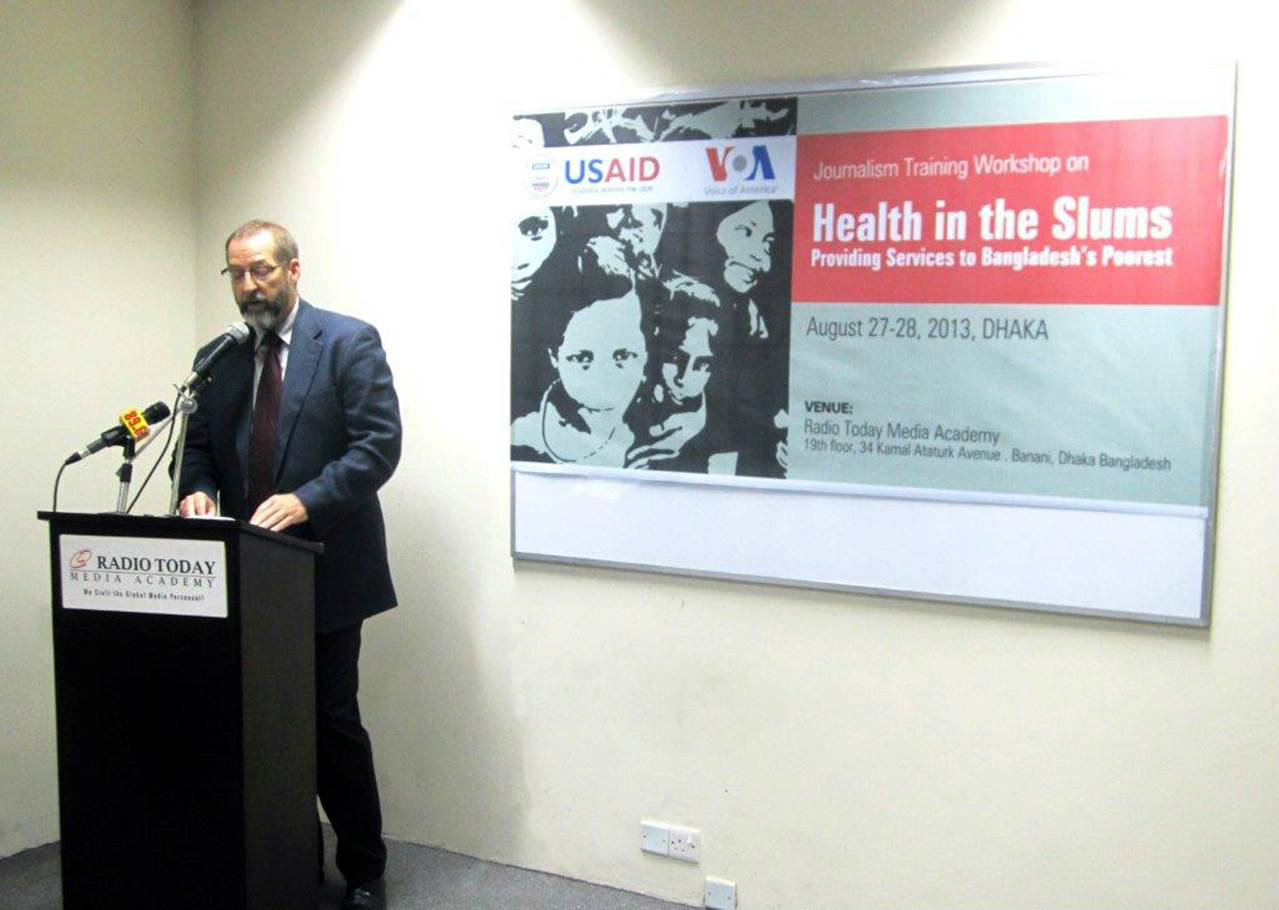 "Man at podium speaks in front of a banner for the ""Health in the Slums"" event"