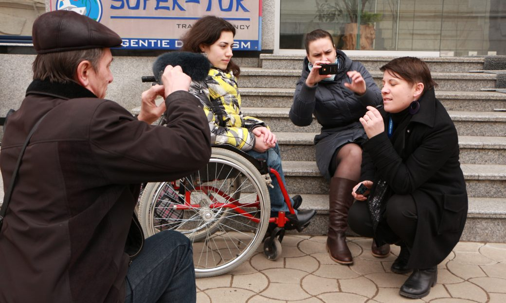 Three journalists training a person on the steps with mobile technology