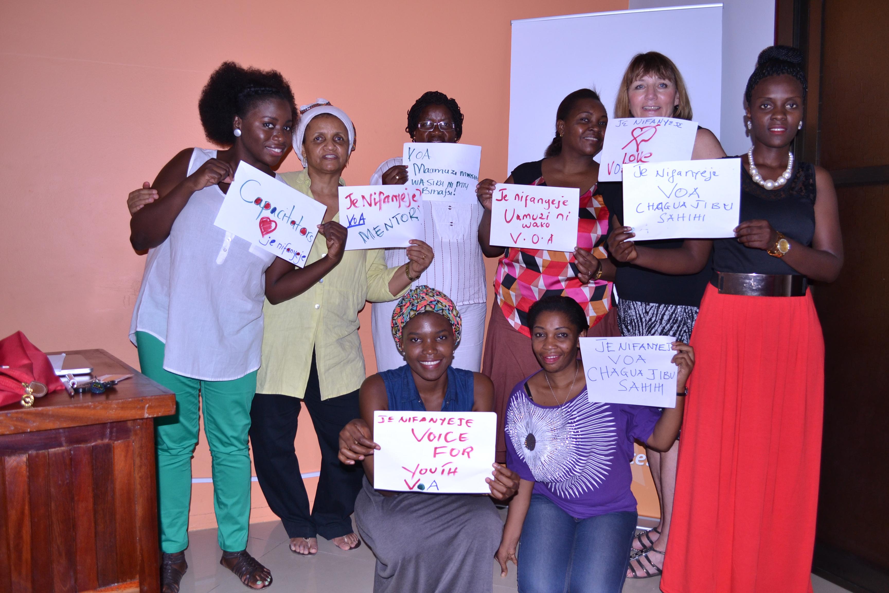 8 women hold handmade signs