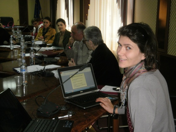 Woman looks back at camera smiling while on her laptop at a conference table with other participants.