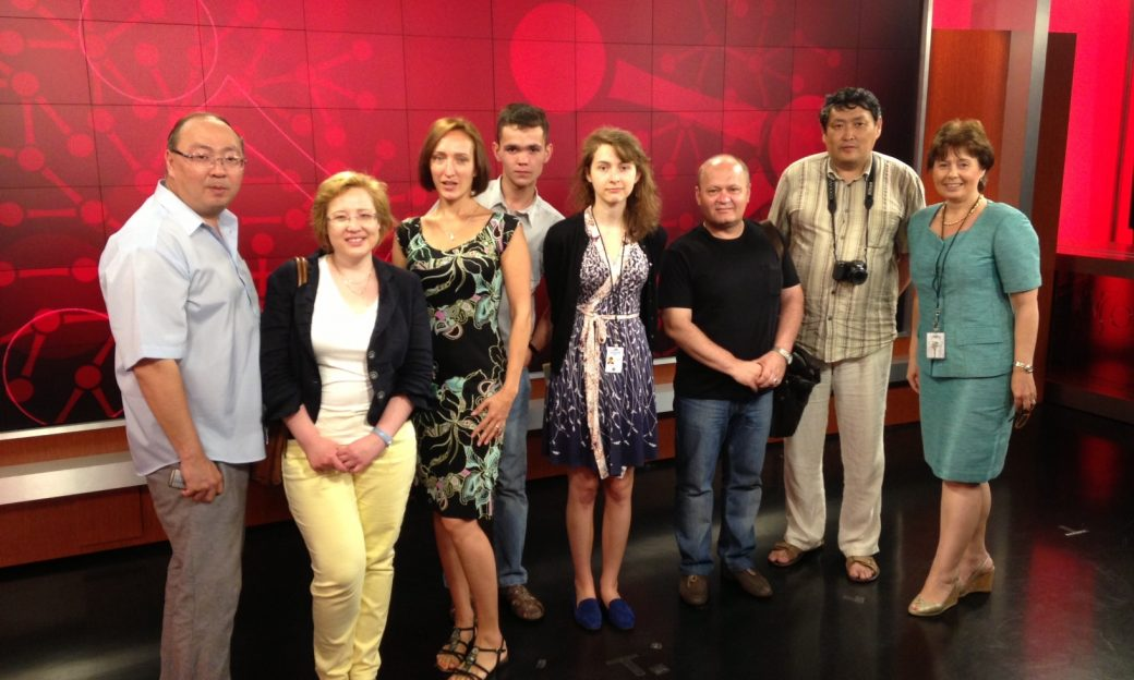 Eight people line up in a VOA studio for a photo
