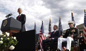 President Obama stands at a podium, uniformed men sit behind him