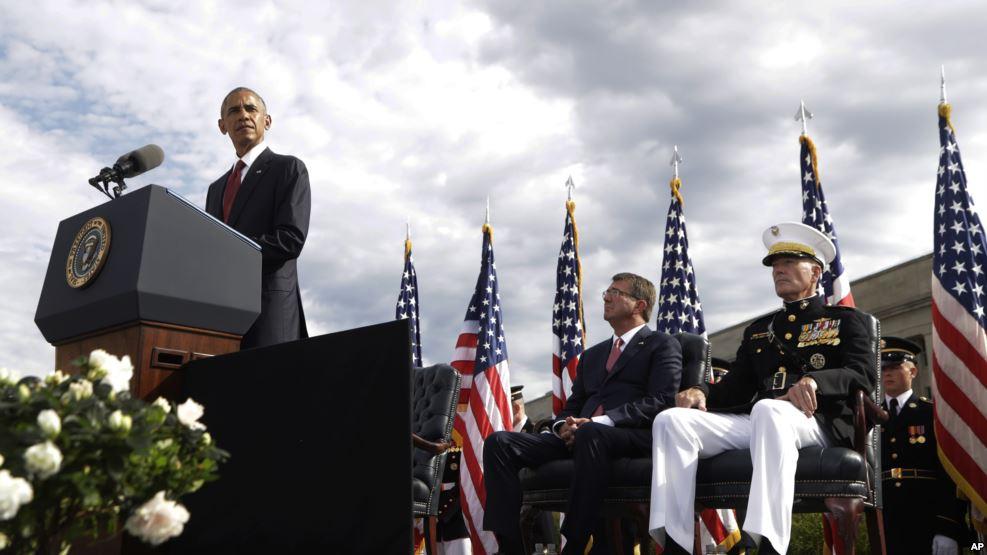President Obama stands at a podium, uniformed men sit behind him