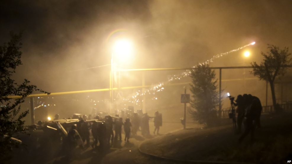 Bright light shines on riot police walking during night time. A light grenade shoots through the sky.