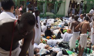 Many people on the ground wearing white with some people standing up