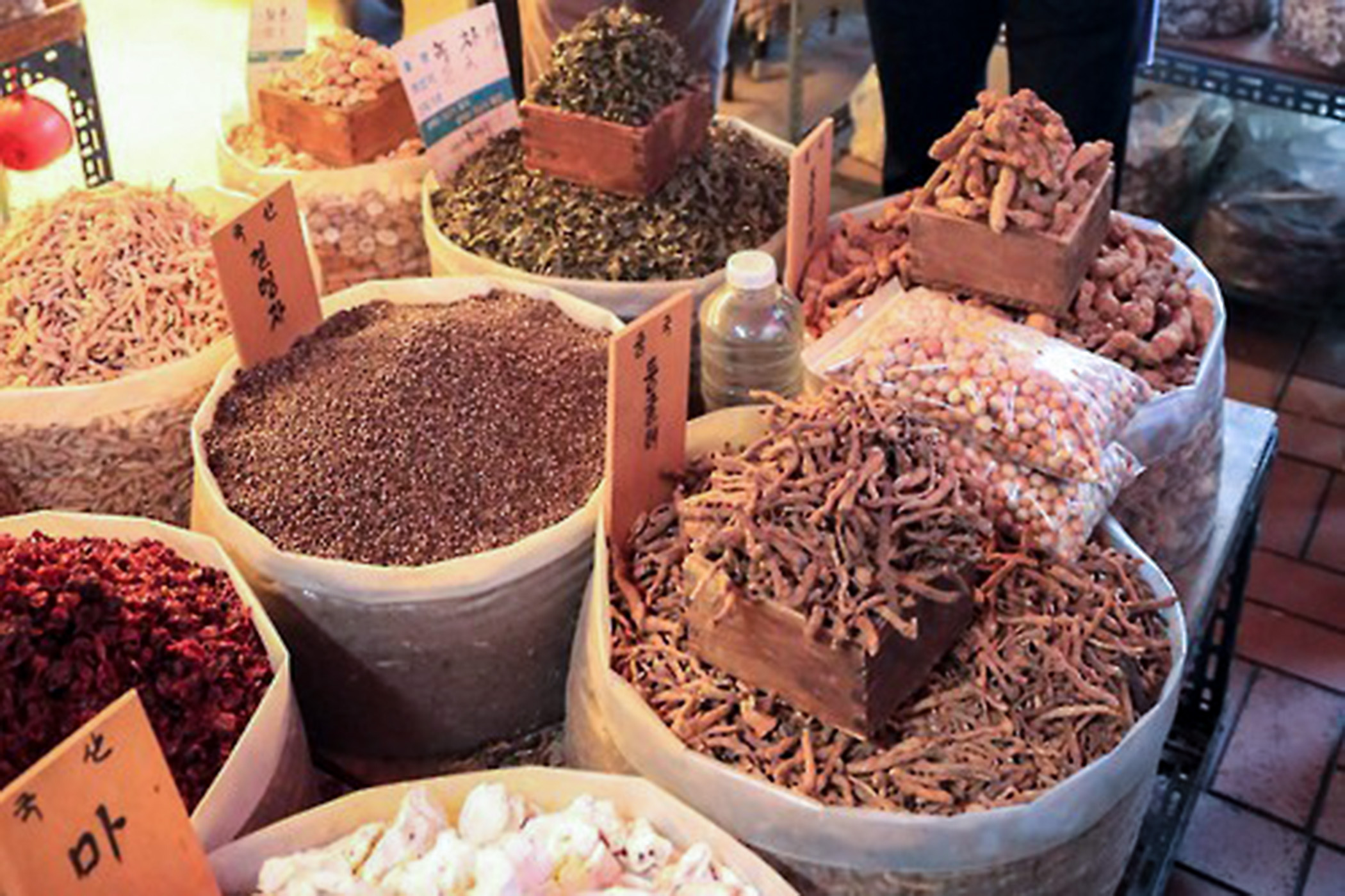 Multiple sacks of mushrooms and other produce at a market