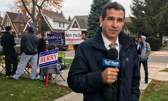 Male reporter in front of election signs on the sidewalk