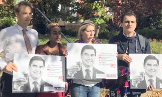 A group of people hold pictures of Saparmamed Nepeskuliev outdoors