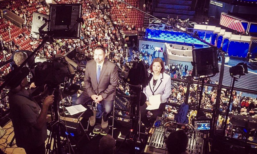 Behind-the-scenes view of two reporters sitting in front of cameras above a crowded auditorium.