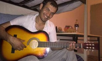 A man plays the guitar in a small room and smiles at the camera.