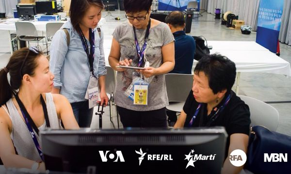 Four Asian women sit or stand in front of a computer screen while having a discussion