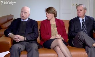 Three U.S. senators, (l-r) John McCain (R-AZ), Amy Klobuchar (D-MN), and Lindsey Graham (R-SC), sit on a couch.