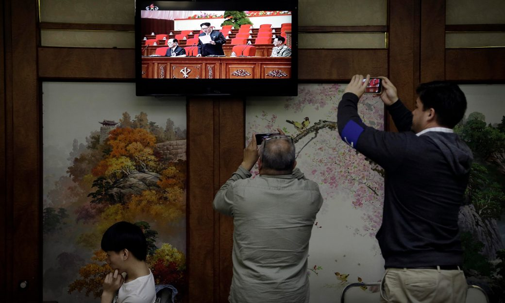 Two men use their smartphones to photograph a television broadcast of North Korean President Kim Jong-Un.