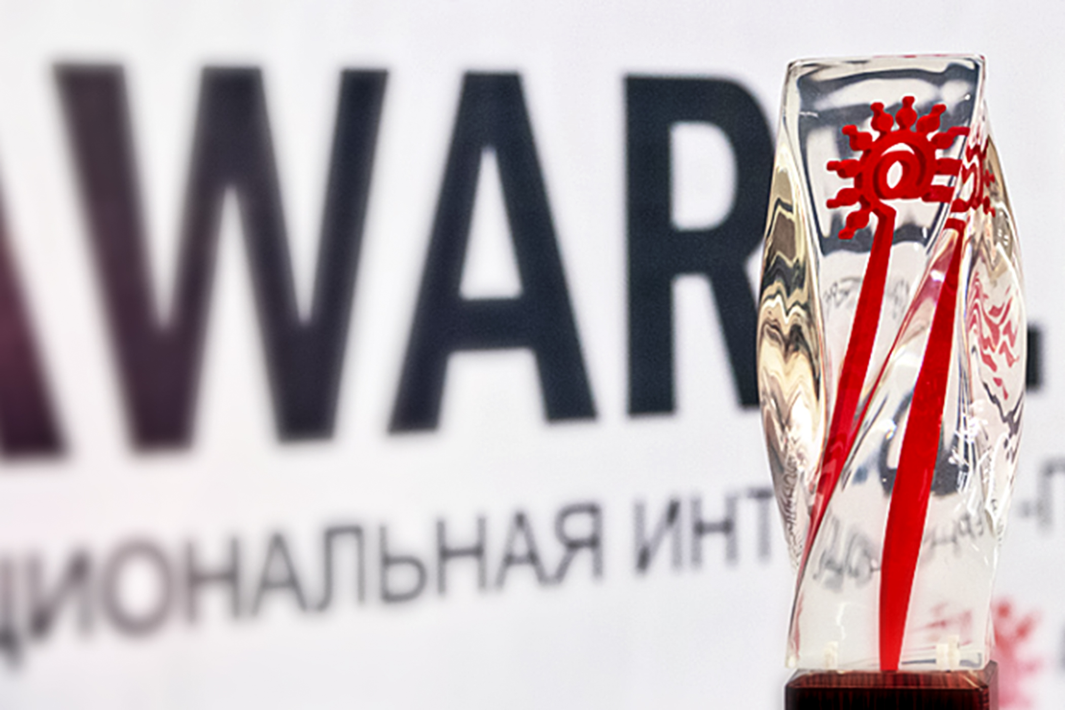 An acrylic trophy in front of a banner for the Award.kz ceremony