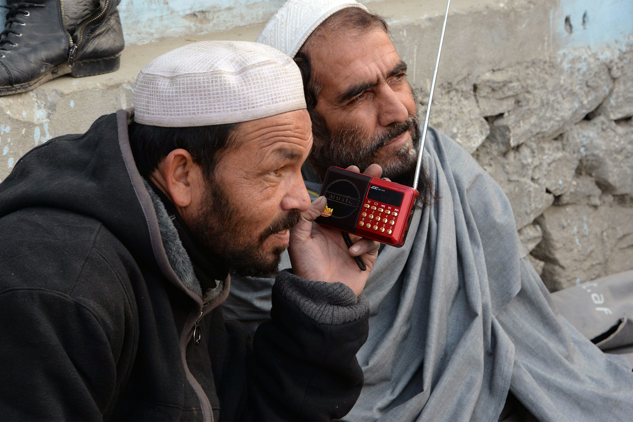 Two Afghan men in white traditional pakol hats listen to a portable radio