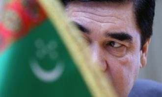Close-up portrait of a man's face behind the flag of Turkmenistan