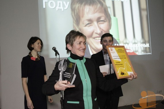 A woman holds an award statuette and holds up a plaque for others to see