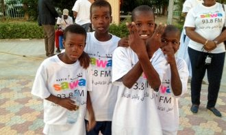 A group of four young African boys pose in Radio Sawa promotional t-shirts outdoors