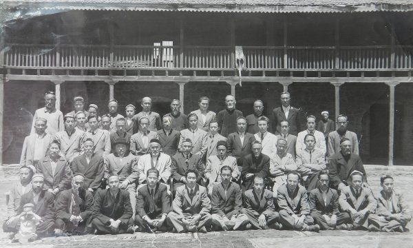 Black-and-white photo of a large group of Asian men posing in 4 rows in front of a building.
