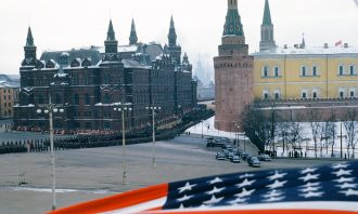 View of a crowd of soldiers standing along a wall of the Kremlin with an American flag in the foreground.