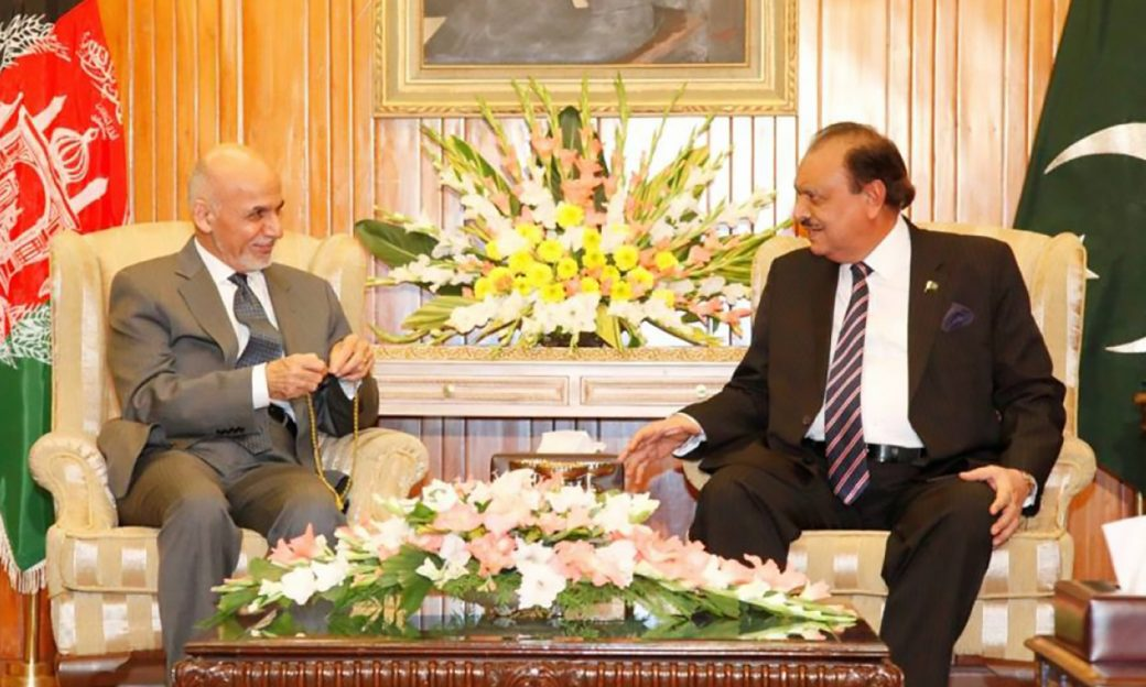 Presidents Mohammad Ashraf Ghani and Mamnoon Husain seated side-by-side with their respective country flags over their shoulders in a presidential office.