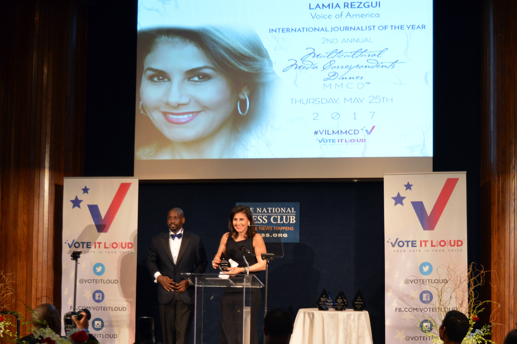 A woman in a black dress holds an award statuette while standing at a podium on a stage next to a black man in a tuxedo