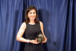 A woman in a black dress holds an award statuette in front of a blue curtain