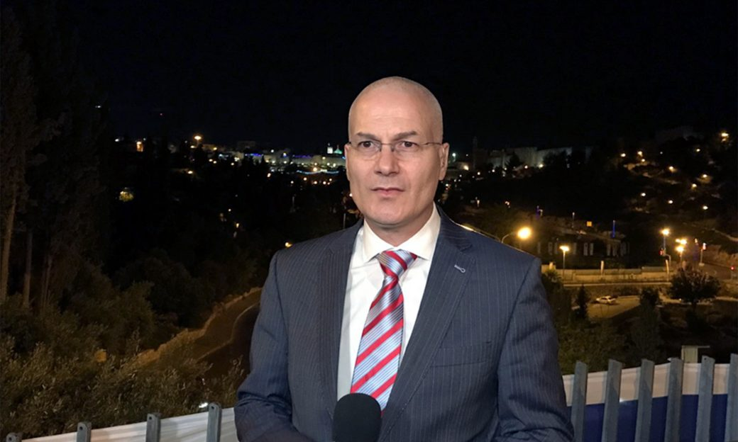 A bald man wearing glasses and a suit holds a microphone at night in front of a cityscape