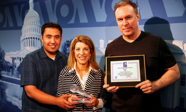 Two men stand on either side of one woman while holding awards and smiling at the camera