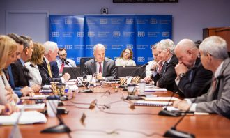 Several senior executives meet at a conference table