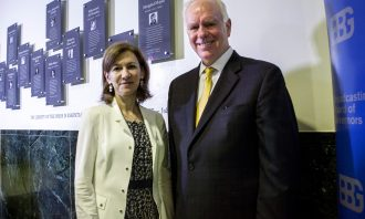 A woman in a blazer and a man in a suit smile at the camera in front of a memorial wall with several photos.