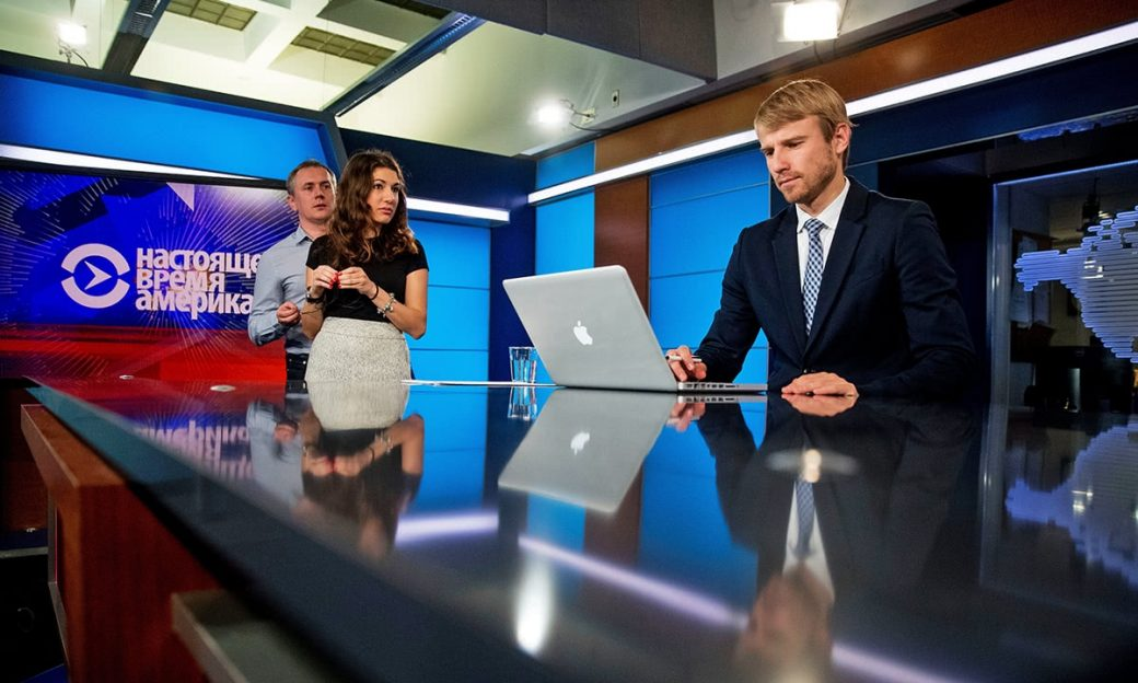 Reporters and news anchors on a news studio set
