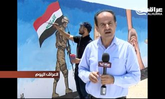 An Arab man paints a mural on a wall in the background while another reports into an Alhurra microphone in the foreground