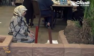 A Muslim woman kneels to pray in a busy restaurant