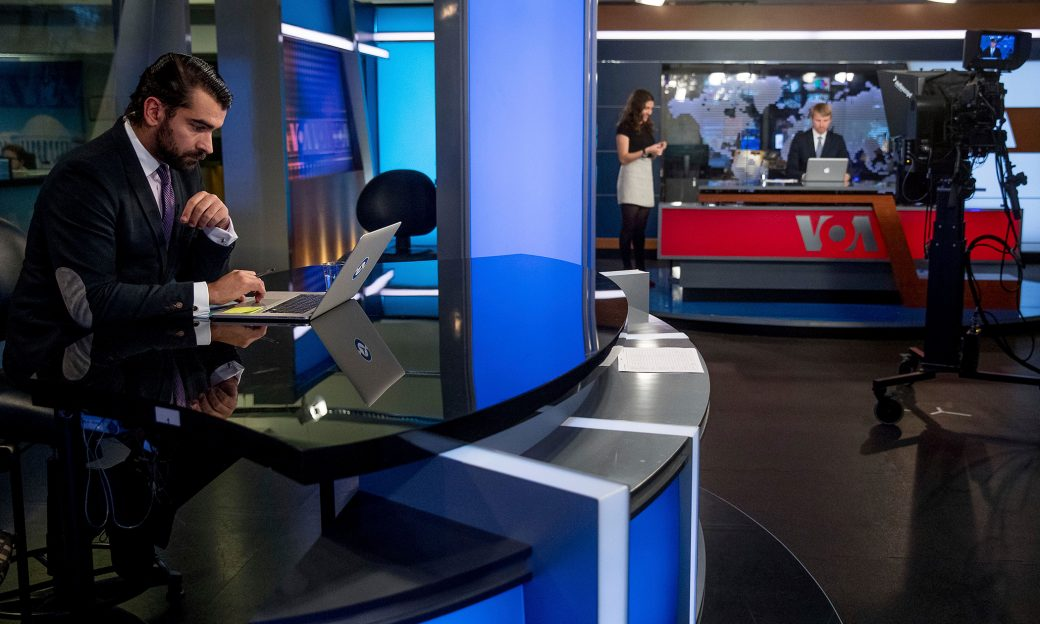 Reporters and anchors in a television news studio set.