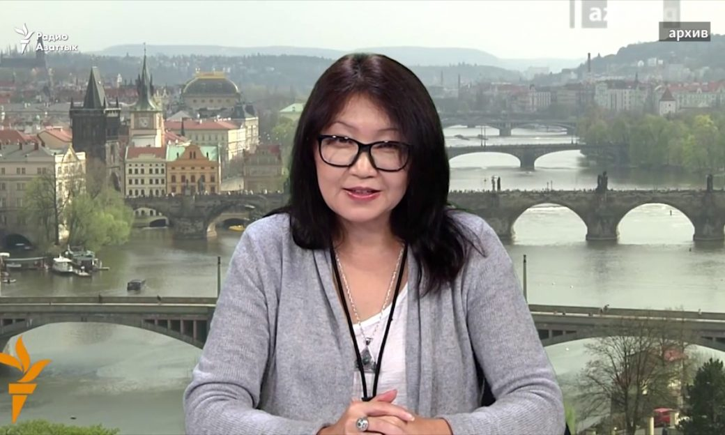 Asian woman sits at a news desk