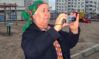 An older woman with a head scarf holds up a small camera while standing in a playground.