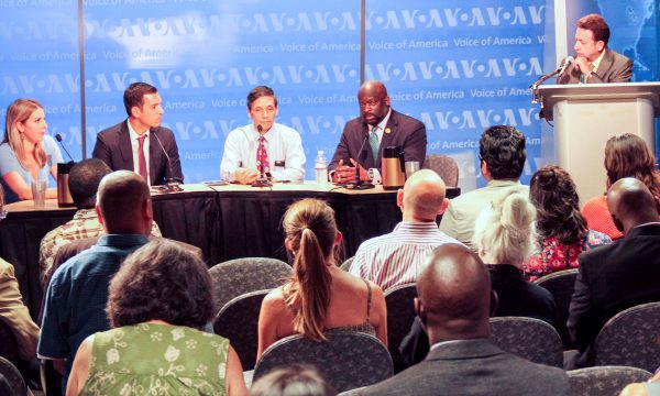 A panel of 4 people sit next to a moderator standing at a podium in front of an audience