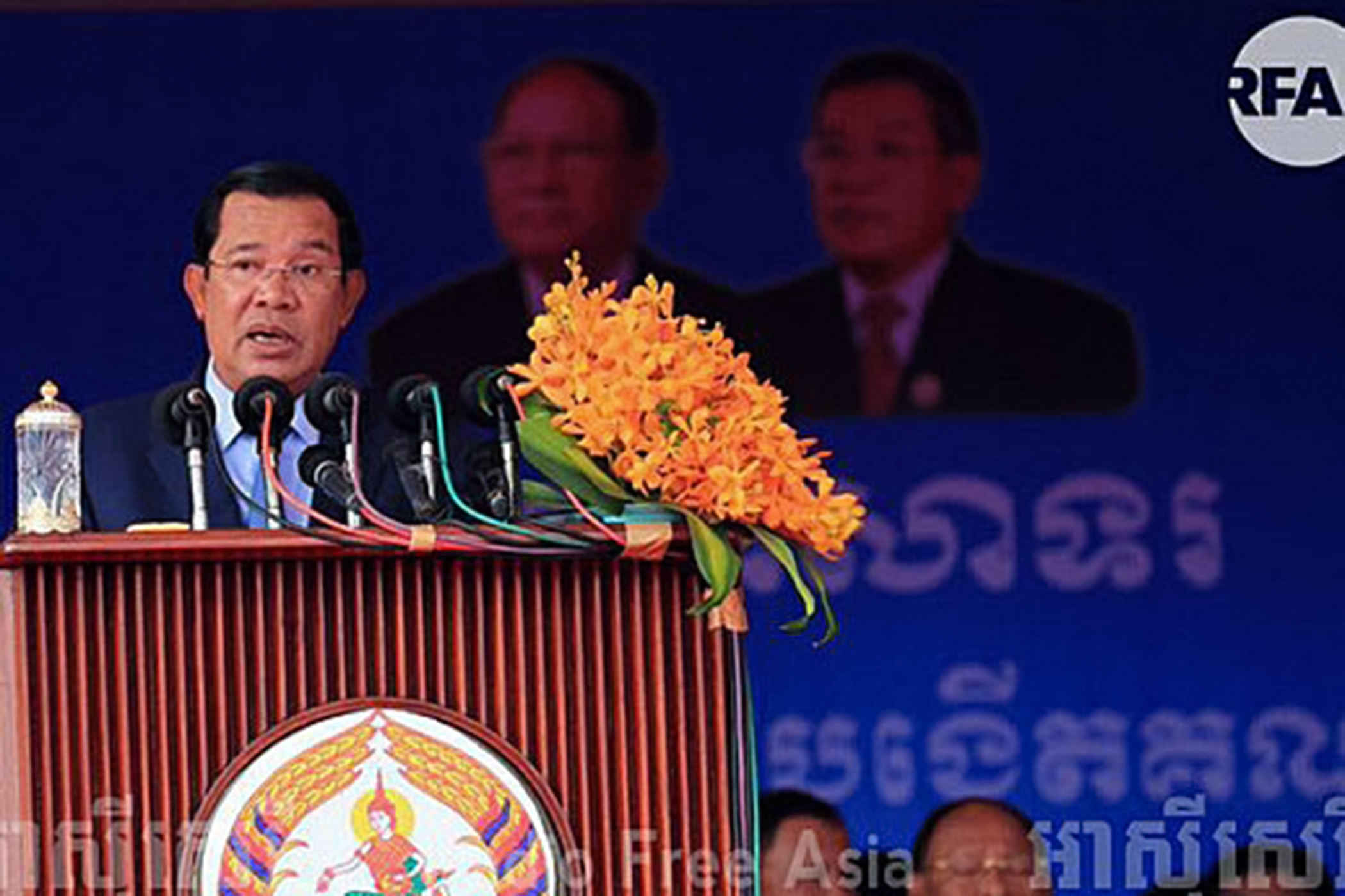 An asian man speaks into a microphone at a lectern