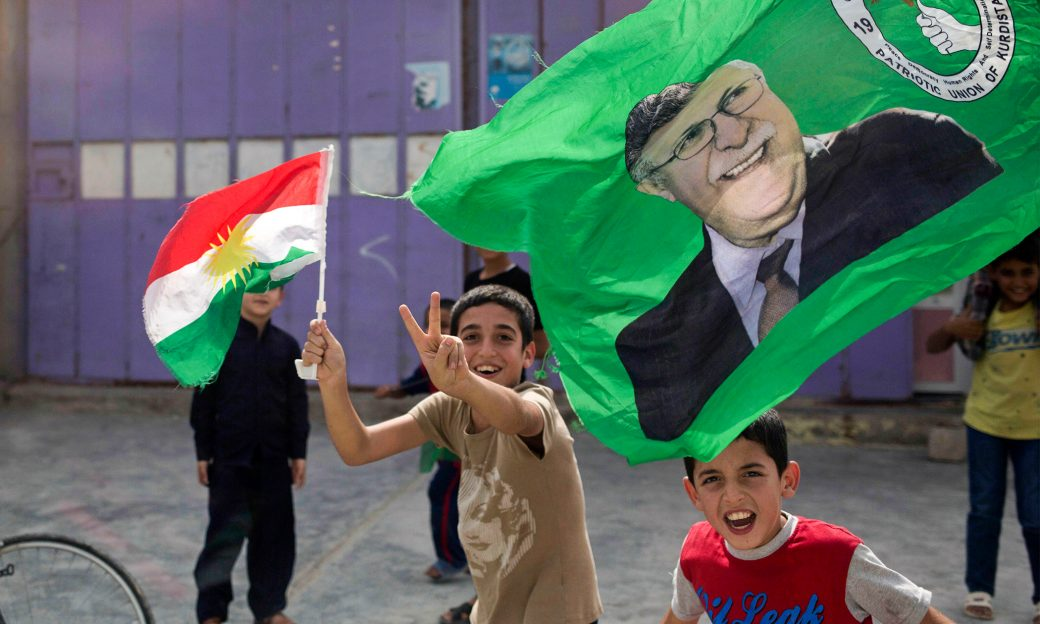 Children holding flags run around and smile towards the camera