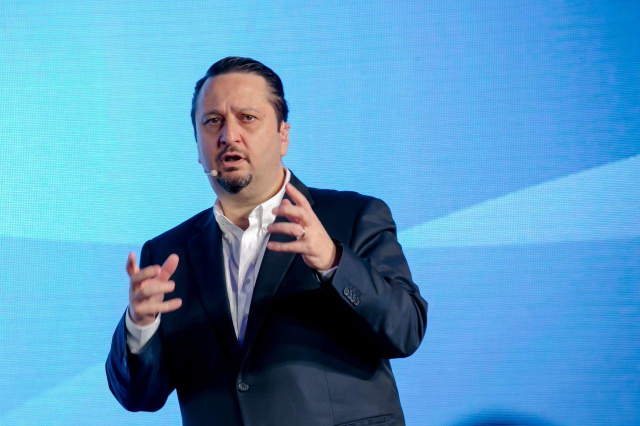 man wearing headset microphone gestures with his hands as he speaks