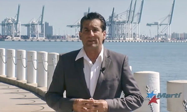a middle-aged man in a gray suit jacket and no tie stands near a bay and large cranes in the distance